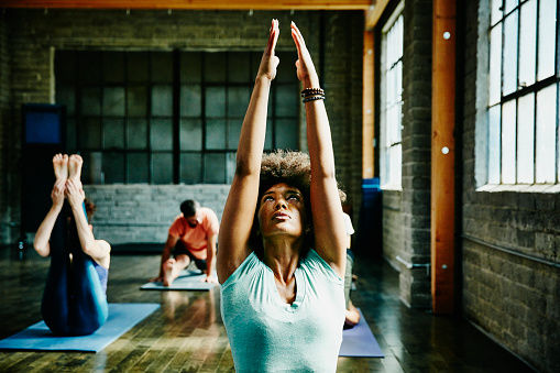 Woman warming up for yoga class with other students in studio
