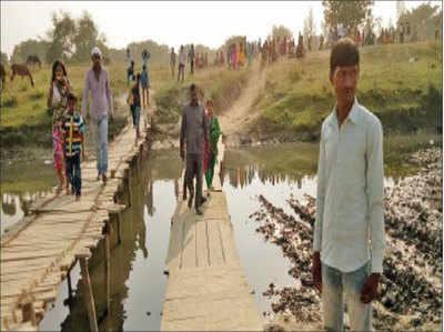 मलिहाबाद में लकड़ी का खतरनाक पुल पार करते लोग