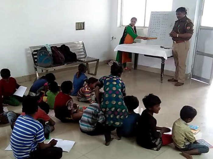क्लास में बच्चों को पढ़ाते पुलिस अधिकारी