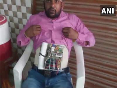 पेट में बंधी इलेक्ट्रॉनिक डिवाइस दिखाता युवक