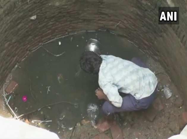 गहरे कुएं में उतरकर गंदा पानी भरता एक ग्रामीण