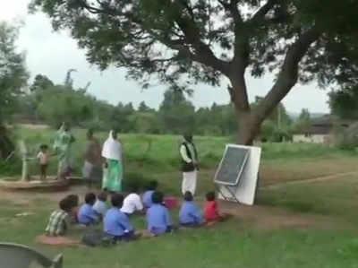 पेड़ के नीचे बच्चों को पढ़ाते शिक्षक