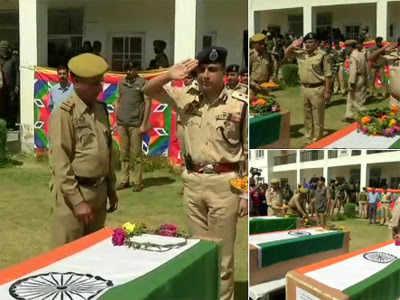 शहीद जवानों को अंतिम विदाई देते पुलिसकर्मी