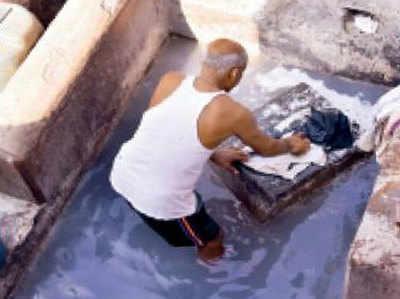 धोबीघाट में कपड़े धुलता धोबी