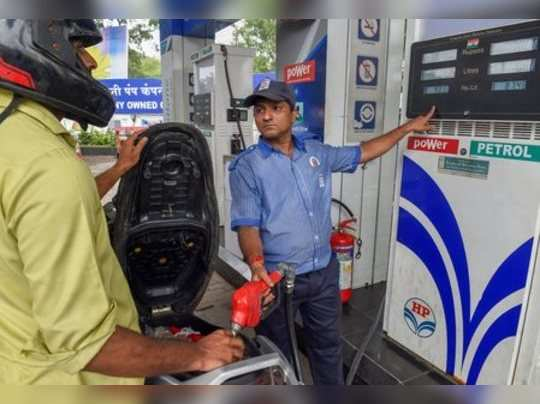 Mumbai: An employee shows the revised prices of petrol and diesel to a customer ...