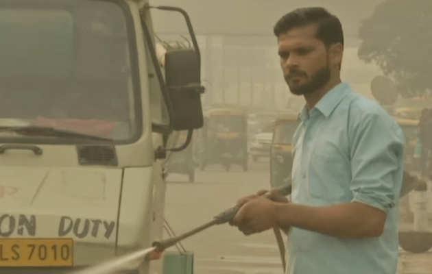 दिल्ली: प्रदूषण से निपटने के लिये पीडब्ल्यूडी कर्मचारी कर रहे पानी का छिड़काव