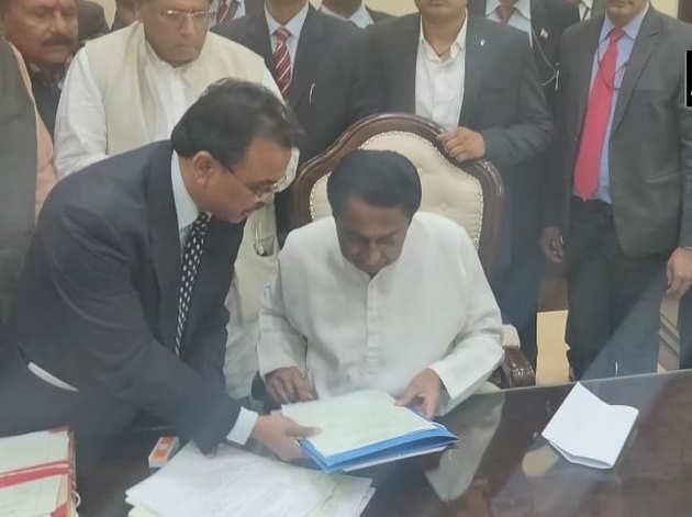 कर्जमाफी की फाइल पर दस्तखत करते मुख्यमंत्री कमलनाथ