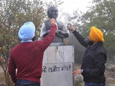 राजीव गांधी की प्रतिमा पर पेंट छिड़कते लोग