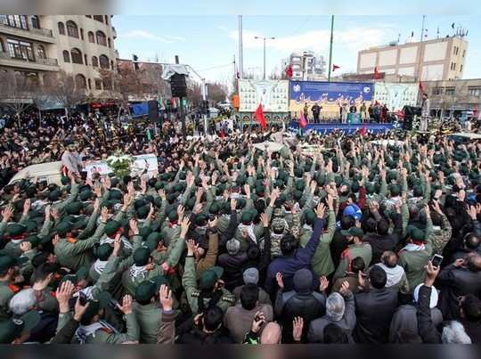 Members of Irans elite Revolutionary Guards, gather around the coffins of their fellow guards, who were killed by a suicide car bomb, during the funerals in Isfahan