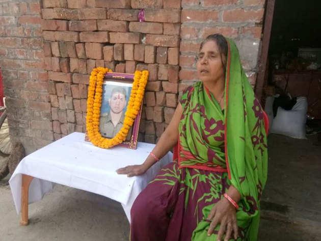 बेटे की तस्वीर के पास बैठीं शहीद की मां
