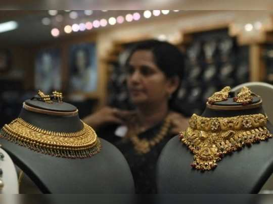 A woman tries on a gold necklace inside a jewellery shop in Hyderabad