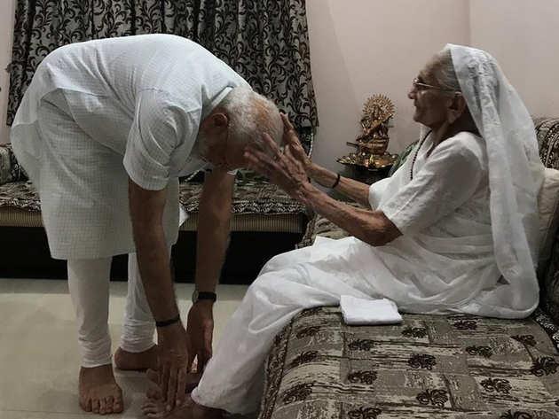 मां के पैर छूकर आशीर्वाद लेते नरेंद्र मोदी