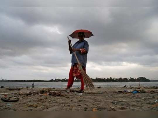 A worker cleans a beach in the backdrop of pre-monsoon clouds at Fort Kochi beach in Kochi