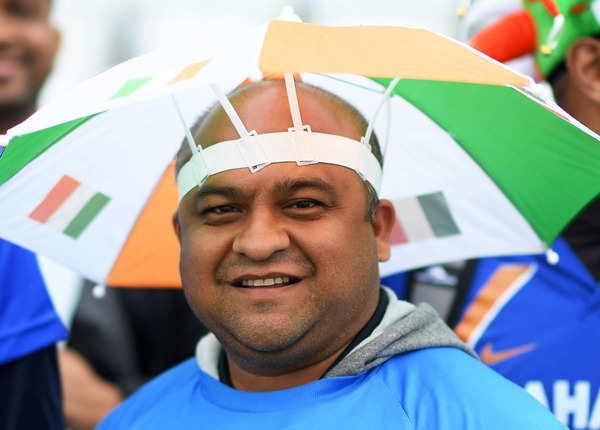 छाता लिए रहे क्रिकेट प्रेमी
