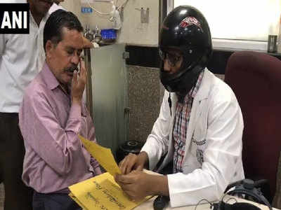दिल्ली एम्स में हेल्मेट पहनकर इलाज कर रहे डॉक्टर
