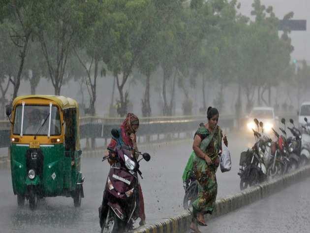 अहमदाबाद में बारिश से बचने की कोशिश करती महिला (एपी फोटो)