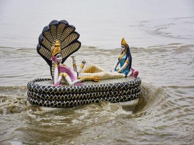 गुवाहाटी में बाढ़ के पानी के बीच घिरी विष्णु प्रतिमा