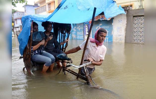 पटना में सवारियां ले जाता एक रिक्शा चालक