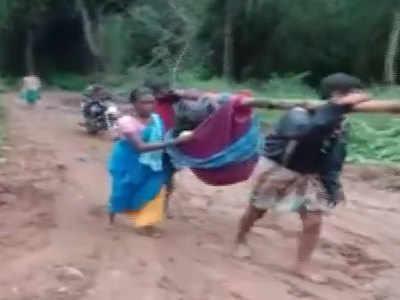 कपड़ों के पालने में महिला को ले जाते ग्रामीण