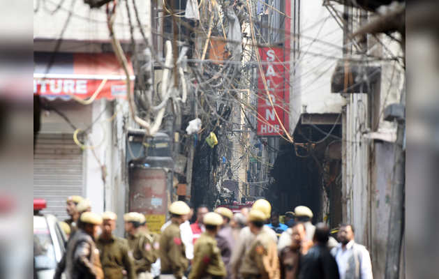 अग्निकांड के बाद घटनास्थल के पास खड़े लोग