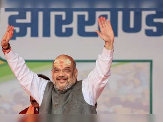 Deoghar: Union Home Minister Amit Shah gestures at his supporters during an elec...