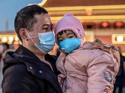 पेइचिंग में बच्चे के साथ मास्क लगाकर खड़ा एक शख्स।