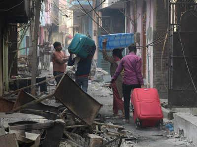 जल चुके घरे से बचा सामान निकालकर दूसरे ठिकानों की ओर जा रहे हैं लोग
