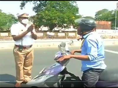राहगीर से हाथ जोड़ता पुलिस वाला।
