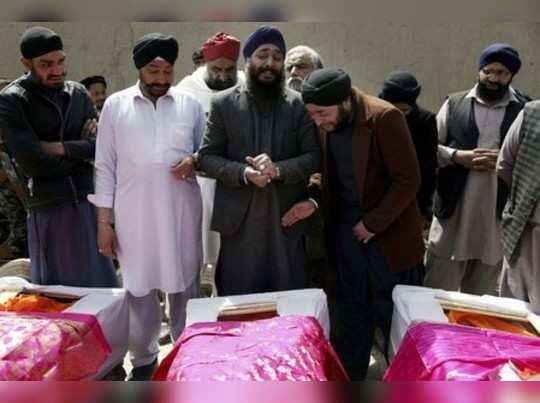 Afghan Sikh men mourn their beloved ones during a funeral