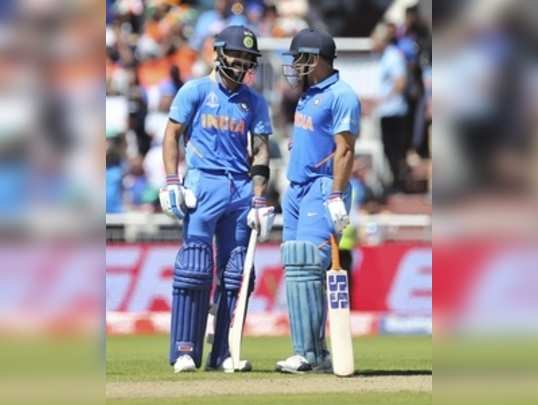 Manchester: Indias captain Virat Kohli, left, and batting partner MS Dhoni sha...