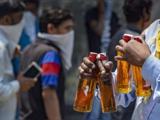 New Delhi: A man walks away after buying liquor from a wine shop that was opened...