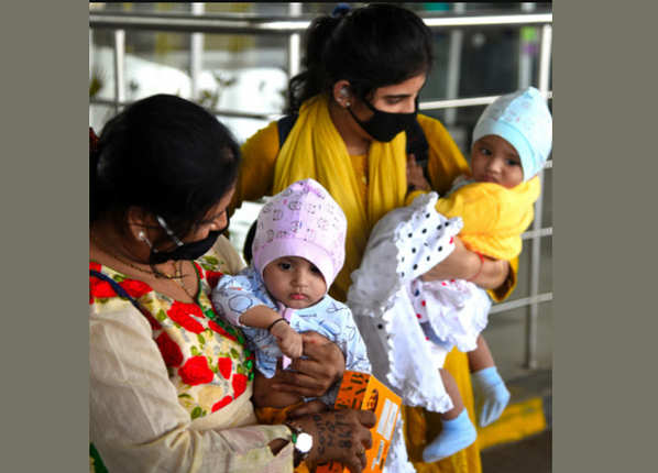 एयरपोर्ट से उतरकर बच्चों को देखती महिलाएं