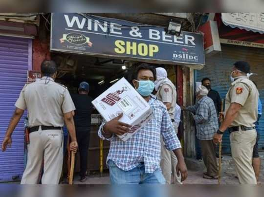 New Delhi: Police keep a watch as people buy liquor from a wine shop at Shiv Pur...
