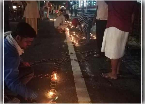अयोध्या में घरों के बाहर दीप जला रहे लोग