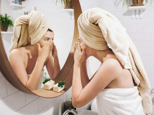 young-happy-woman-in-towel-applying-organic-face-scrub-and-looking-at-picture-id1126244497