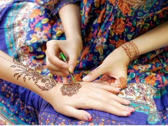 young-woman-mehendi-artist-painting-henna-on-the-hand-picture-id600997670