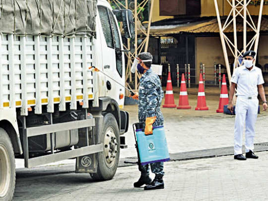 An official of the Kochi naval base disinfects an inter-state truck at the main entrance to the base on Tuesday