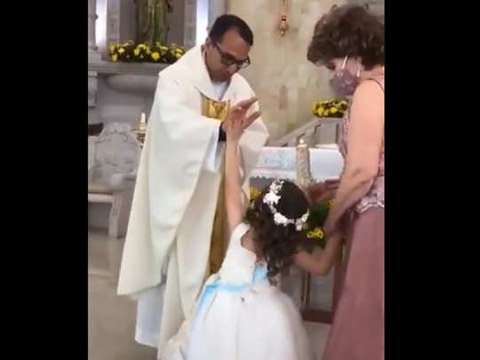 Girl giving high-five to priest