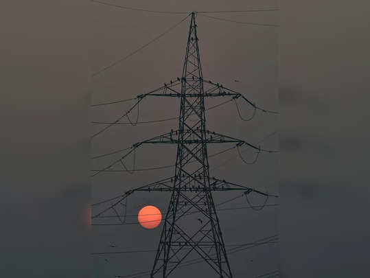 New Delhi: An electric tower is silhouetted against the setting sun, in New Delh...