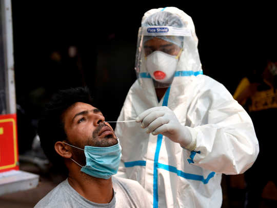A health official wearing a Personal Protective Equipment (PPE) suit collects a swab sample from a man to test for the COVID-19 coronavirus in New Delhi AFP