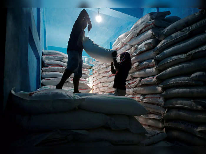 Labourers lift a sack filled with sugar