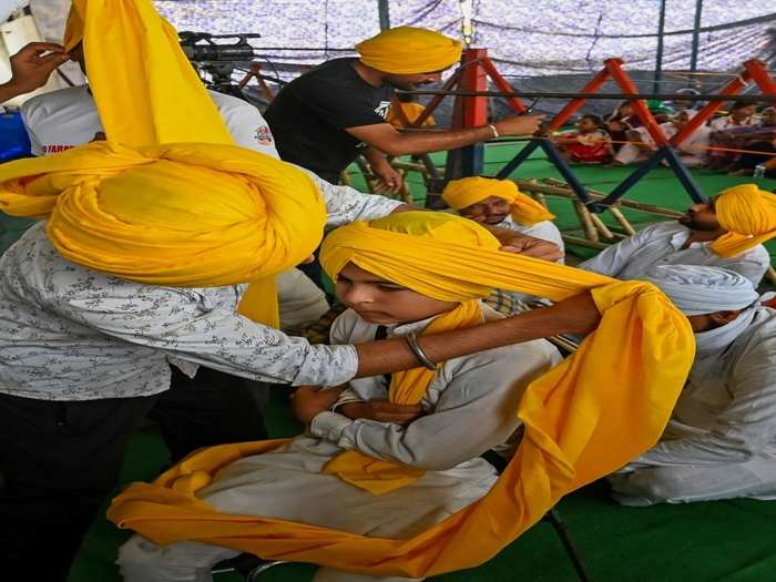 protesting farmers tie yellow coloured turbans or headgear to mark the martyrs day as they continue their protest along blocked highway against the central government