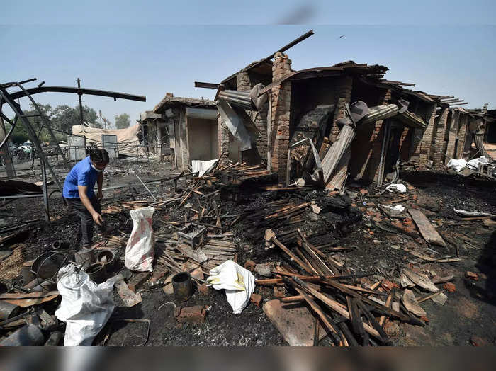 New Delhi: A shopkeeper stands near the debris of shops destroyed due to a fire ...