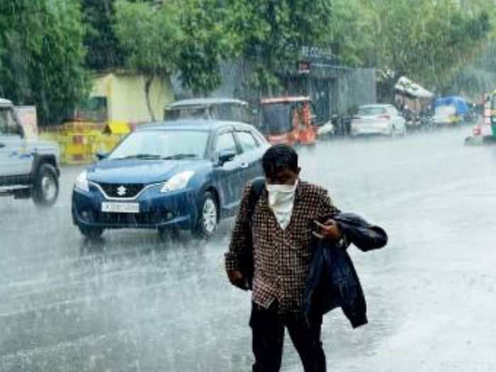 A man rushes to take shelter from rainfall in Jaipur on Monday