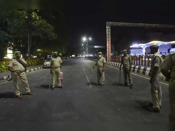 Lucknow: Police personnel guard on a road during a night curfew, imposed amid su...