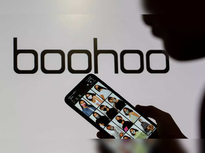 FILE PHOTO: A woman poses with a smartphone showing the Boohoo app in front of the Boohoo logo on display in this illustration