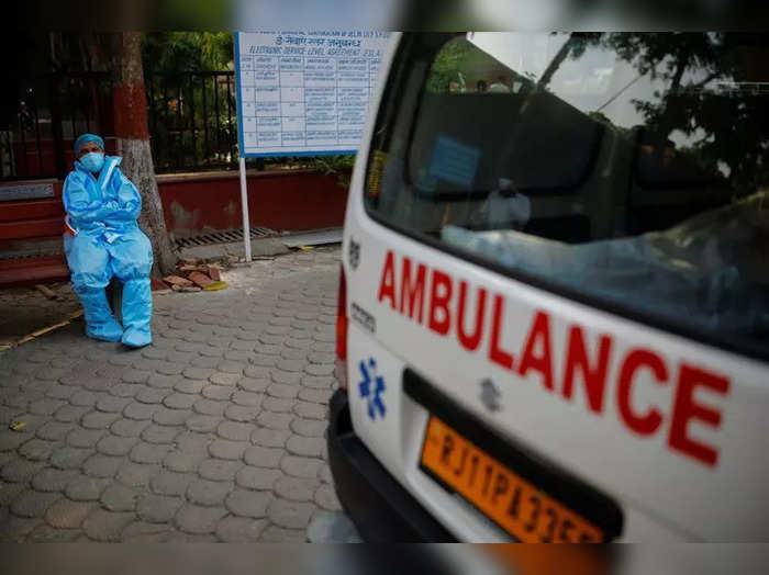 A health worker rests as he sits next to his ambulance carrying a dead body of a victim who died due to the coronavirus disease (COVID-19), at a crematorium