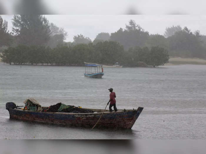 A fisherman stands in his boat ahead of Tropical Cyclone Jobo, at the Kunduchi ward in the Kinondoni district of the Dar es Salaam