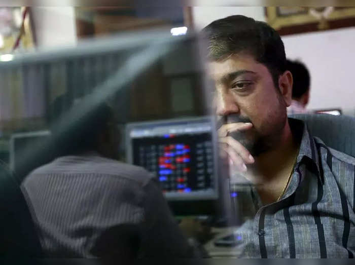 A broker reacts while trading at his computer terminal at a stock brokerage firm in Mumbai
