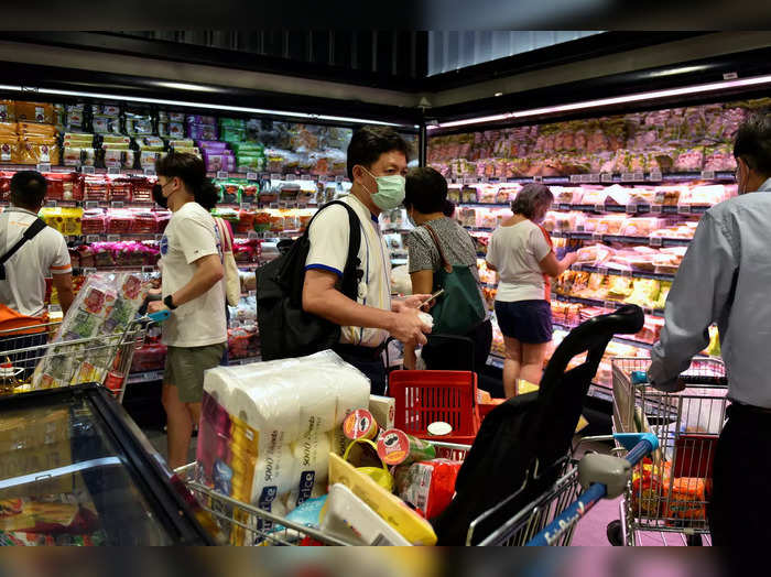 People shop for groceries at a supermarket after curbs on social gatherings and public activities were announced following a rise of coronavirus disease (COVID-19) cases in Singapore